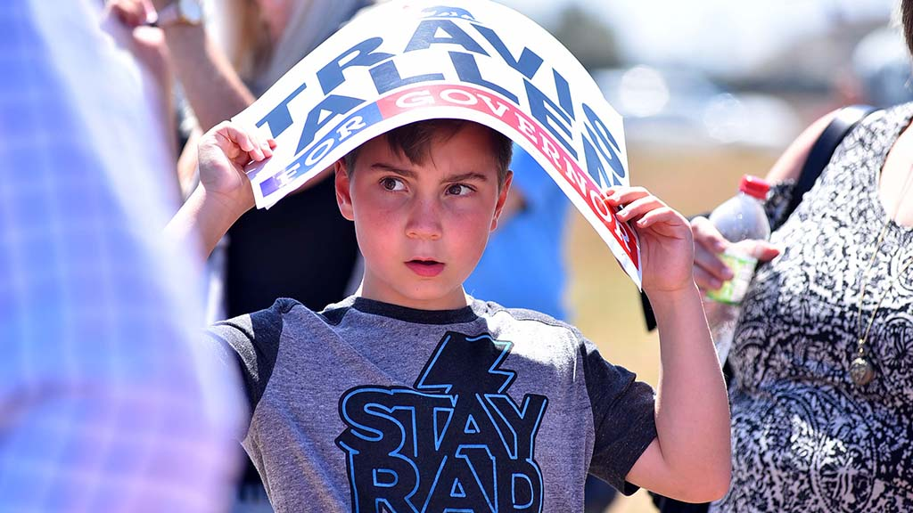 A child uses a Travis Allen poster to protect himself from the bright afternoon sun.