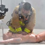 A firefighter demonstrates CPR techniques on a dummy.