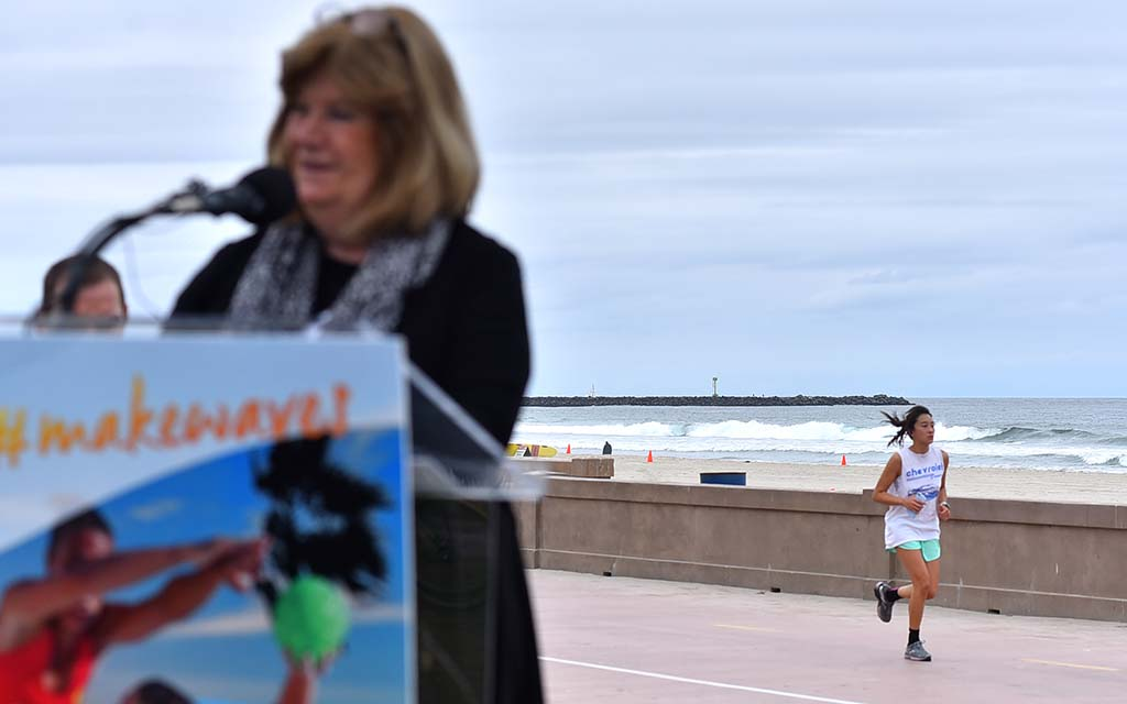 A jogger passes Lorie Zapf during her remarks on the third anniversary of San Diego seeking the World Beach Games.