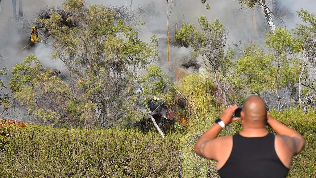 Resident Jason Torralda watches as the Adobe fire blazes on the other side of drainage ditch from his home.