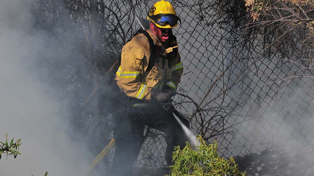 A firefighter puts out flames close to a housing development in Del Cerro.