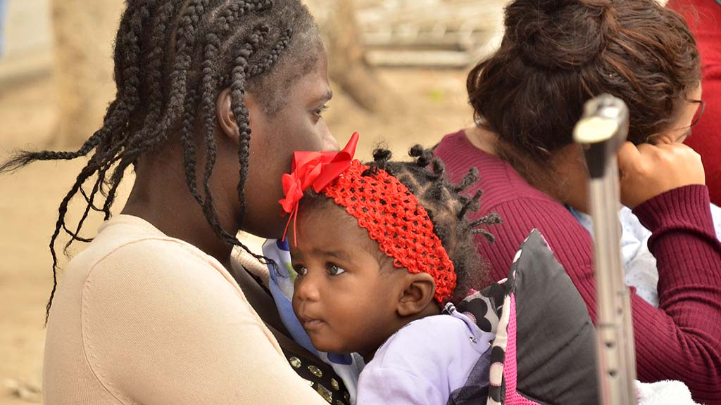 A woman from Haiti and her child wait outside the port of entry although she wasn't on that day's list.