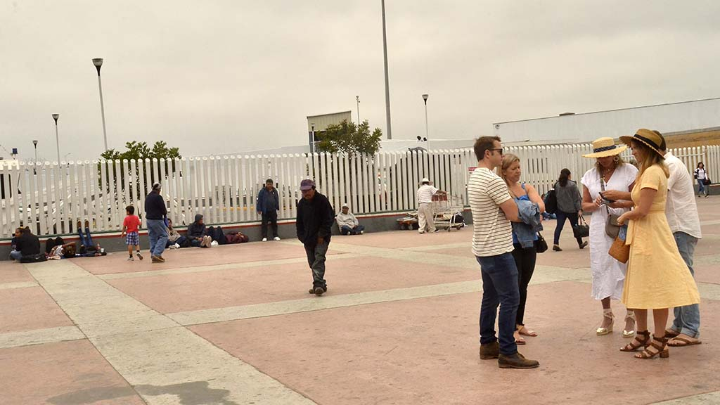 While tourists plan their visit in Mexico, families wait along the wall for asylum.