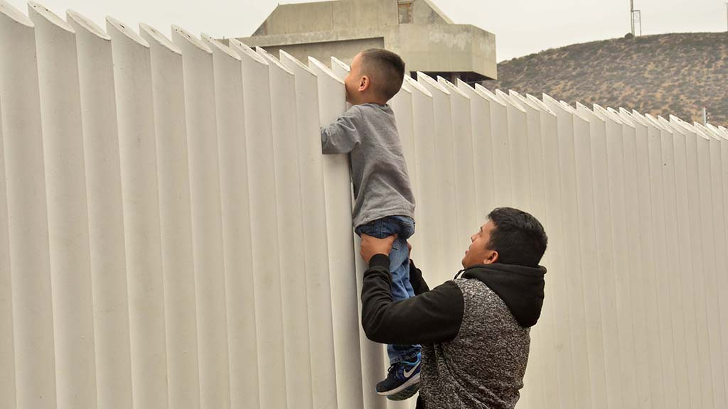 A man holds up a child who peeks into U.S. territory.