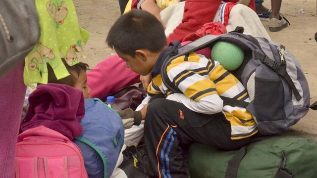 A child, with a ball tucked behind is back, waits with his family at the border.