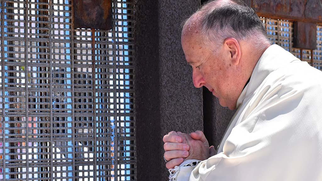 San Diego Bishop Bishop Robert McElroy prays at the U.S.-Mexico border fence.