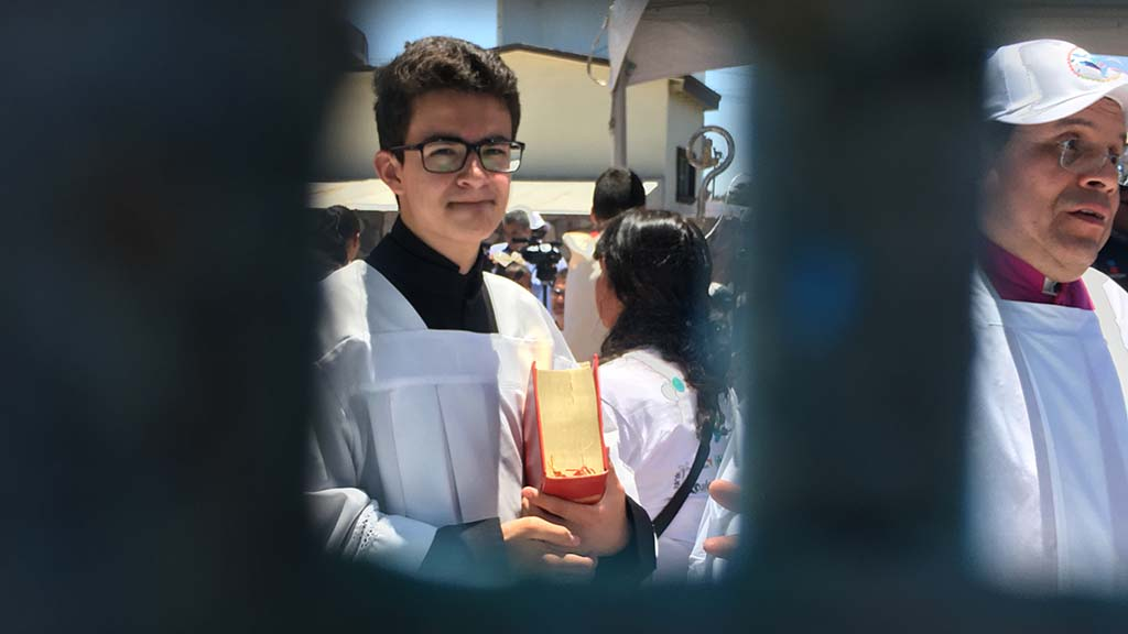 An altar server with a liturgical book is seen on the Mexican side of the border before the binational Mass.