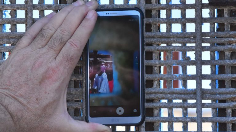 Associate Bishop John Dolan captures video of the Mass on the Mexican side of the border fence.