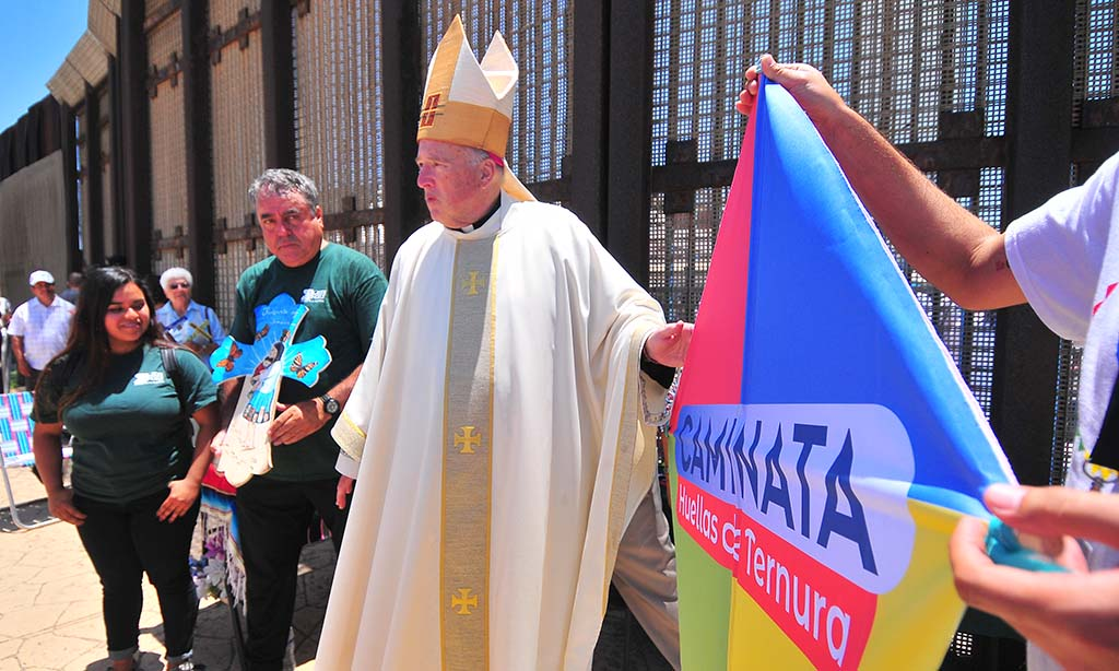 Enrique Morones holds a cross and San Diego Bishop Robert McElroy gets ready to bless the kite.
