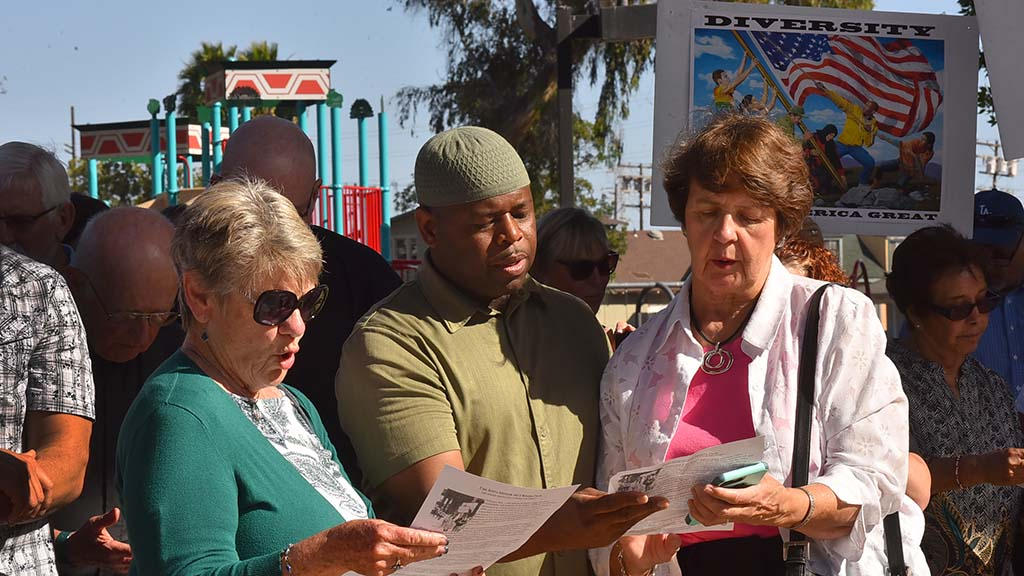 Carole Morales of Rancho Santa Fe, Yusef Miller of Escondido, and Margie Carroll (left to right) recite a prayer at Chicano Park.