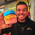 Tony Boghosian of Chicken Charlie's shows off the ice cream sandwich with vanilla ice cream sandwich pink and blue cotton candy and rolled in Fruity Pebbles.