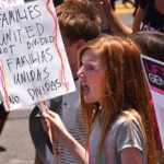 A young girl protests immigration policy in downtown San Diego.