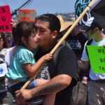 A father kisses his daughter during a march against the Trump Administration's immigration policy.