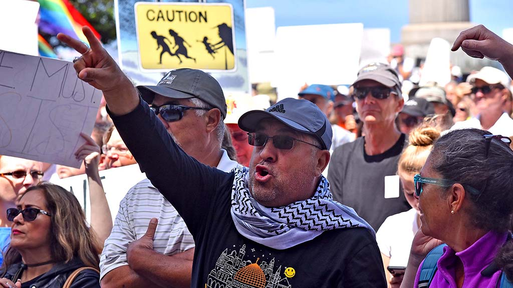 A protestor signals his approval at a Families Belong Together rally at Waterfront Park in San Diego.