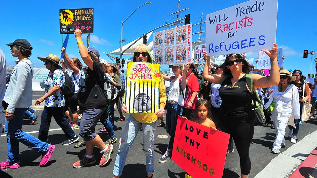Protestors carry their homemade signs to protest immigration policy.