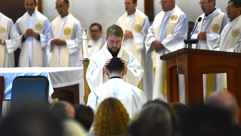A Jesuit lays his hands on O. Alejandro Baez-Gonzalez during the ordination.