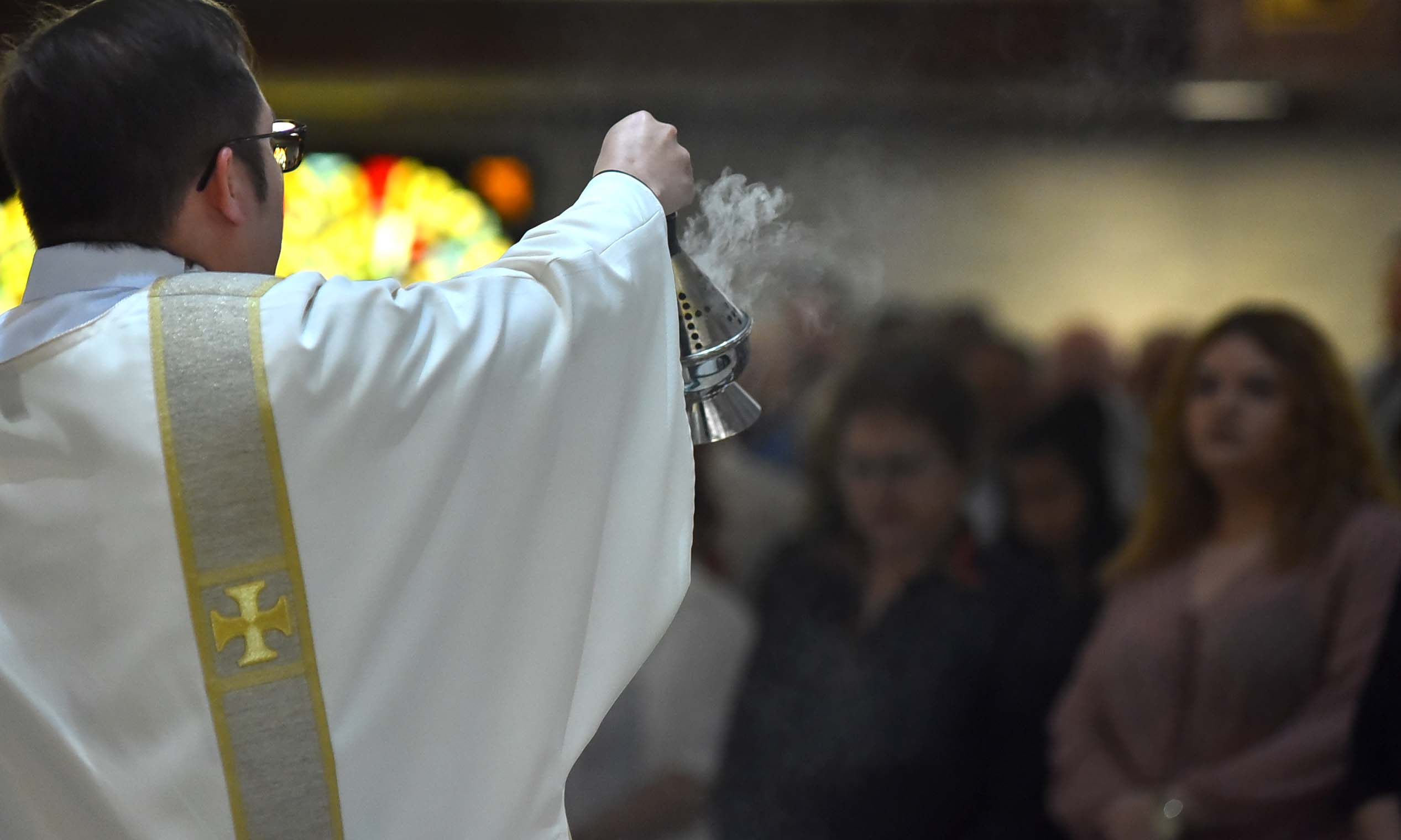 A priest swings incense toward parishioners.