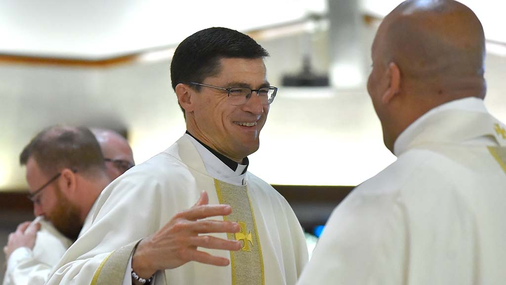 The Rev. Scott Santarosa, provincial for Jesuits West, greets Elias Puentes, who was ordained.
