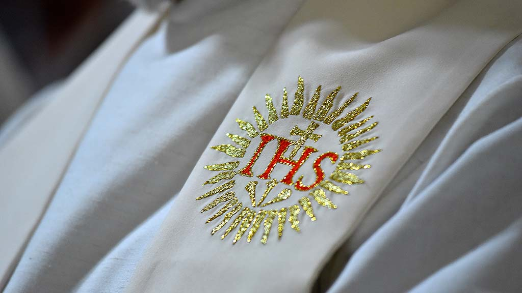 An embroidered symbol of Jesus Christ is seen on a Jesuit priest's stole.