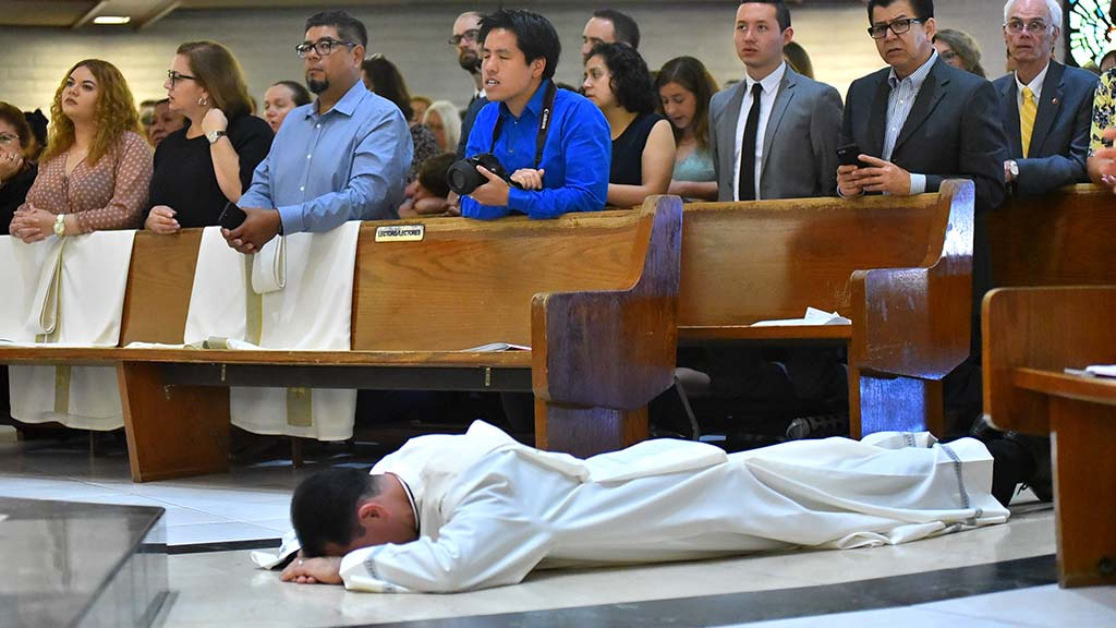 One of the four men to be ordained as a Jesuit priest prostrates himself as a sign of submission and humility during the ceremony.