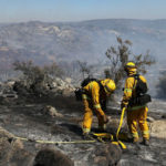 Firefighters on a charred hilltop