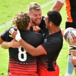 Nick Boyer, center, is congratulated by his teammates after a try.