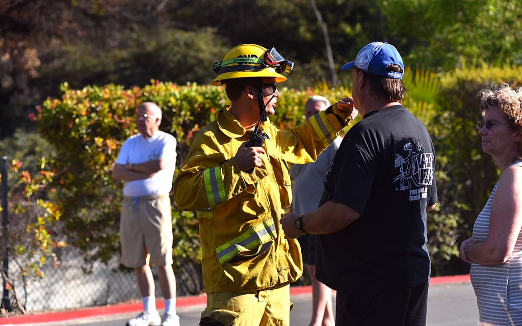 San Diego firefighter calms residents on status of fire near Adobe Falls Road.
