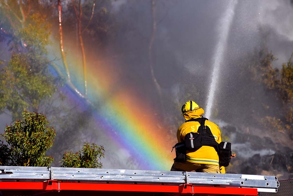A San Diego firefighter's hose creates a rainbow while battling a brush fire near Adobe Falls Road north of Interstate 8.