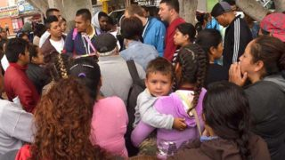 Refugees gather early in the morning to consult a member of the Mexican Institute of Migration about their place in asylum line.