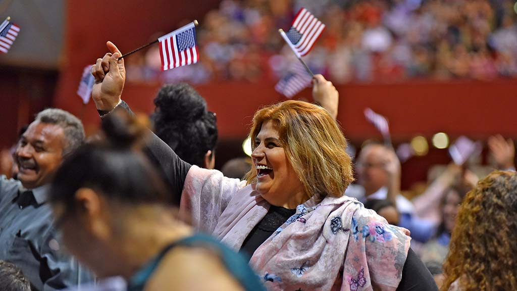 New citizens from Mexico wave American flags at the oath ceremony at Golden Hall.