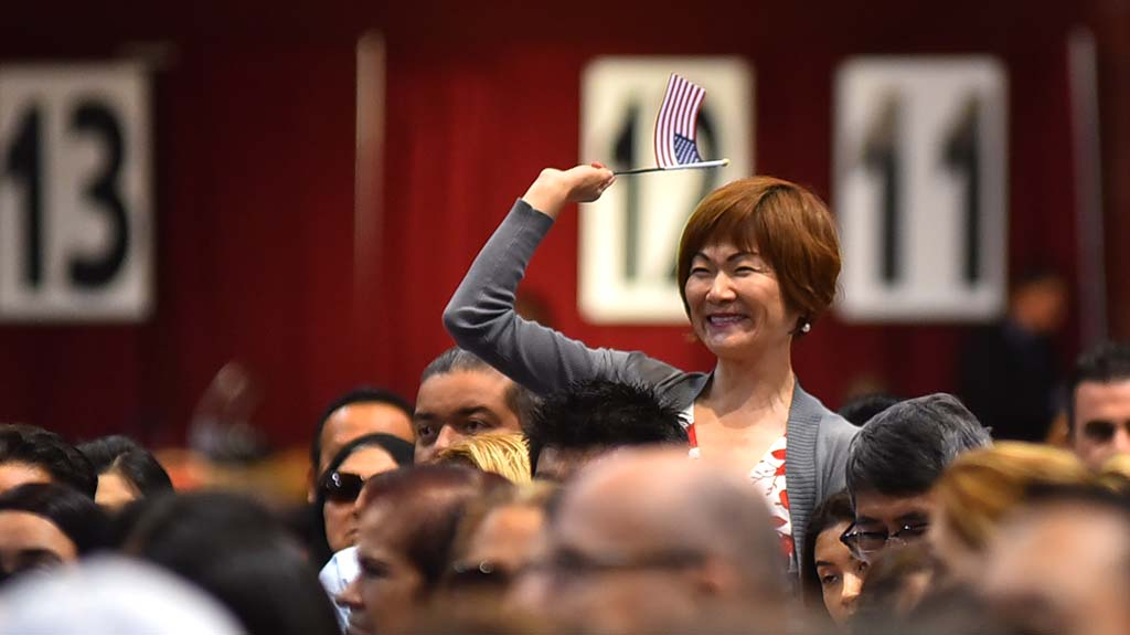 A woman from Japan waves her American flag as her country of origin is called.
