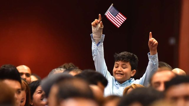 A young relative of a new citizen cheers from the crowd of immigrants.