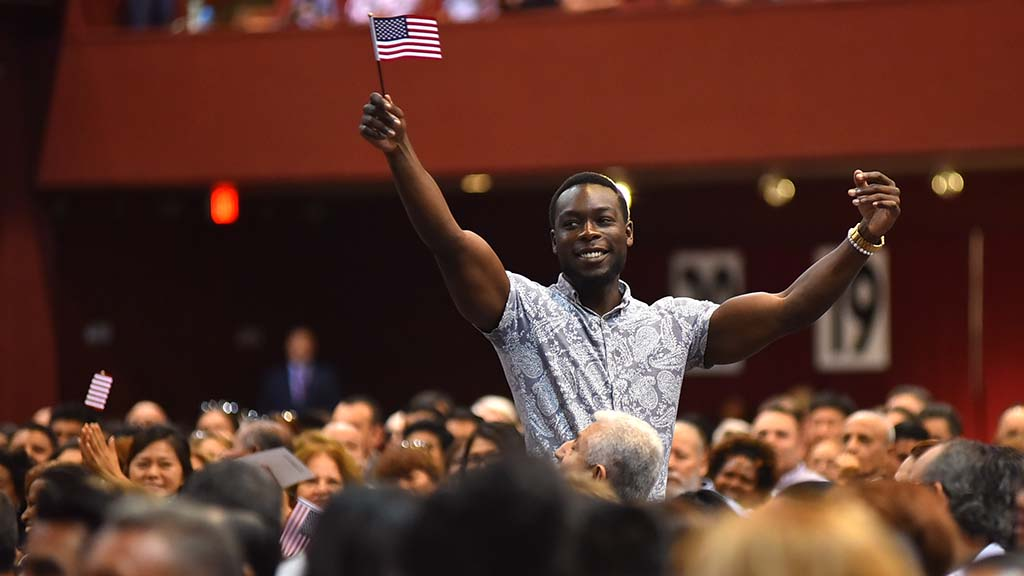 An immigrant from Zimbabwe, the lone representative from his country, waves his flag proudly.