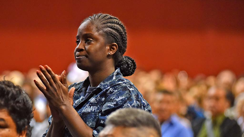 A member of the Navy was one of three immigrants at the ceremony who received her citizenship through her military service.