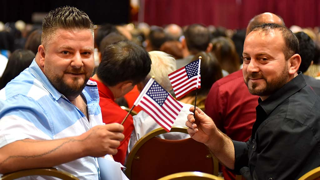 Iraqi brothers Bashar Farida (left) and Remon Farida proudly wave their American flags at the oath ceremony.