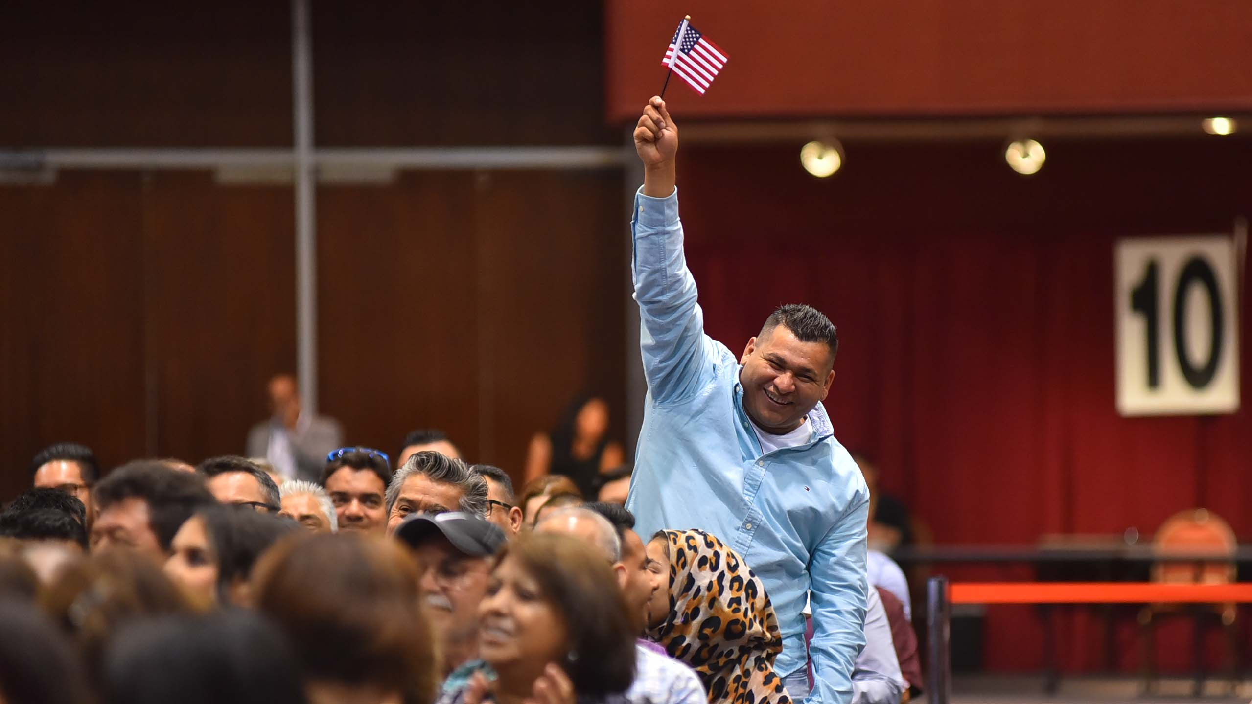 A man from El Salvador proudly represents his country as the judge calls out names of countries at the oath ceremony.