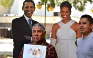 Eulogio Saldivar (left) and his son, Joel, pose with cutouts of the Obamas after the ceremony.