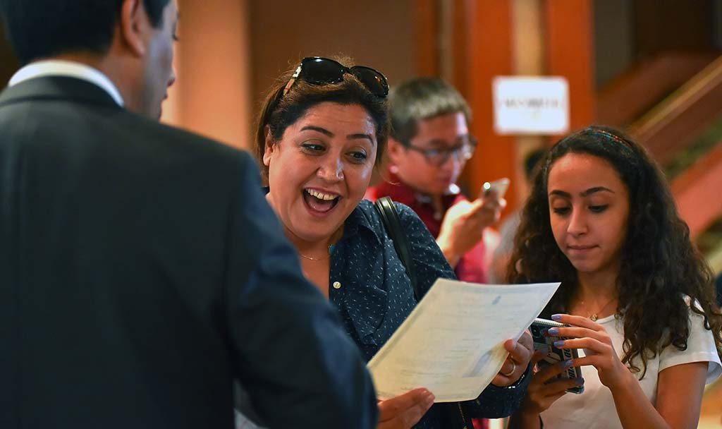 A woman reacts to a relative's naturalization certificate.
