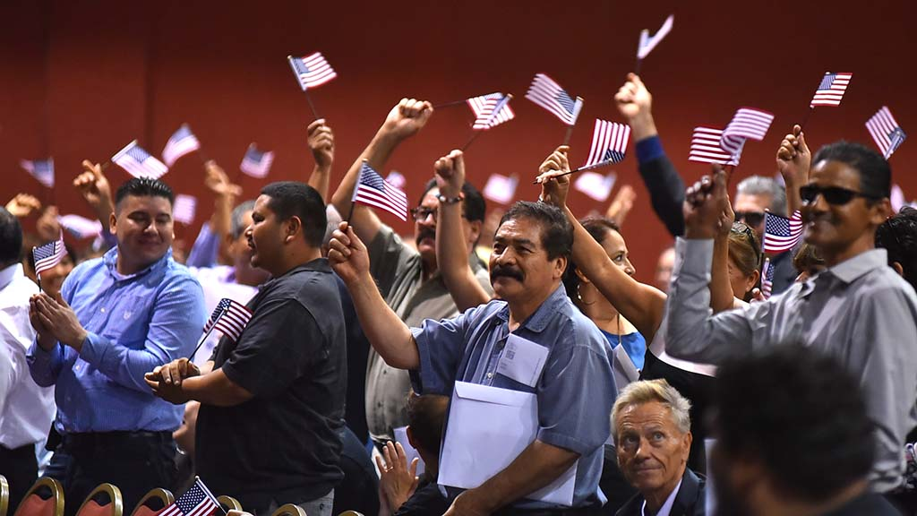 New citizens from Mexico stand and wave American flags as their country of origin is called before the oath ceremony.