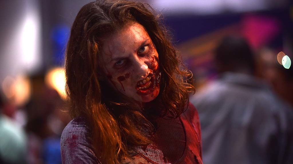 An actress spooks attendees at the Walking Dead booth in the exhibit hall.