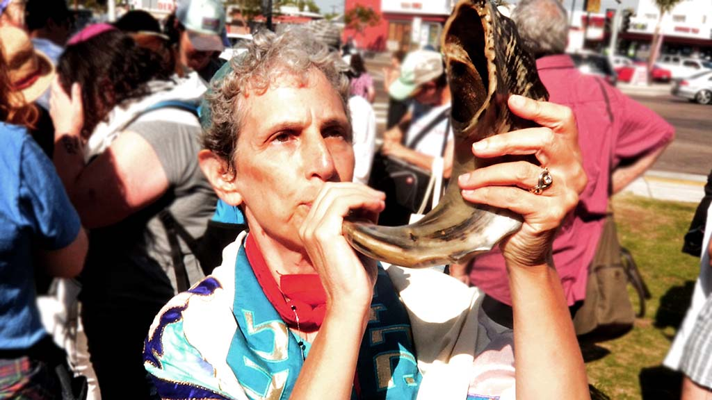 Rabbi Shifrah Tobacman, a healthy housing program manager i the San Francisco Bay Area, blows a Shofar before the rally and march.