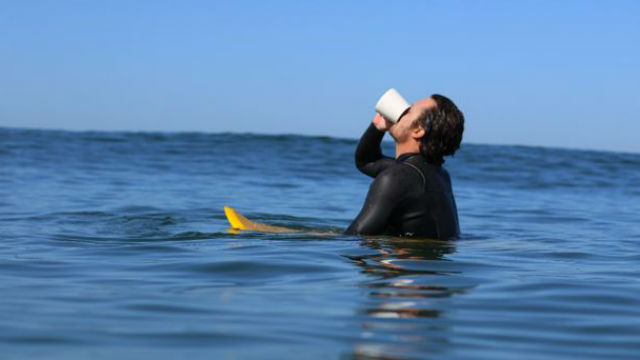 Surfer drinking coffee on his board
