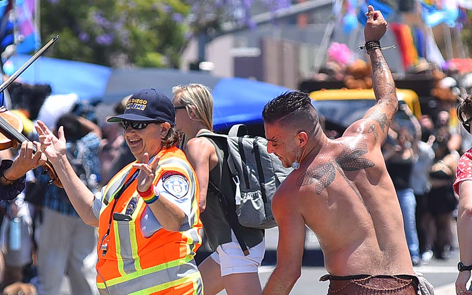 A parade participant dances with a San Diego Police traffic officer.