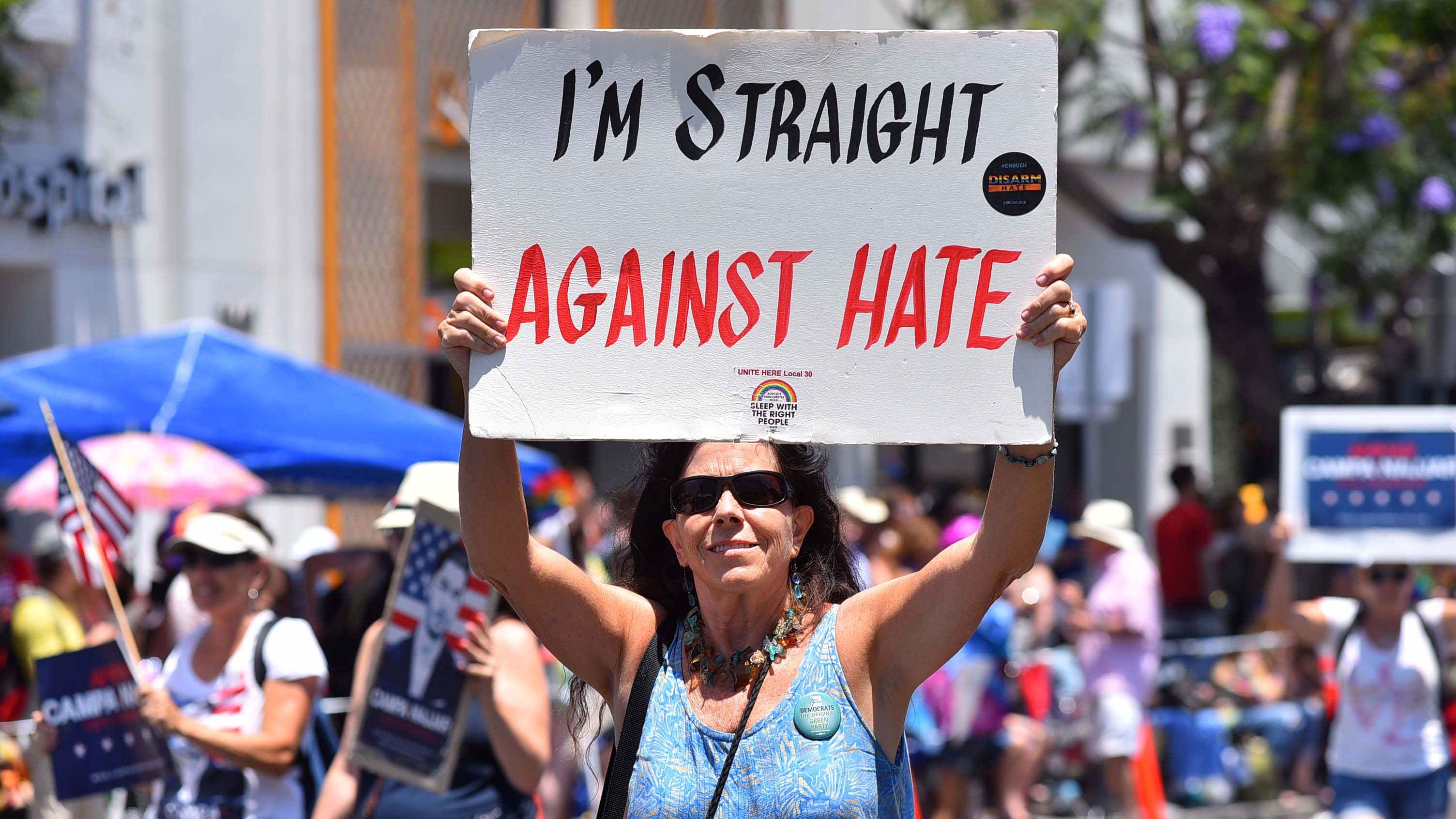 A member of a Democratic contingent carries a supportive sign for gay pride.