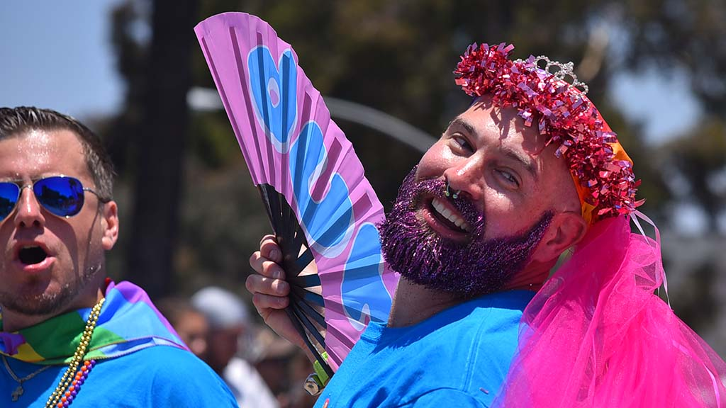 A parade participant displays his fan and smile.