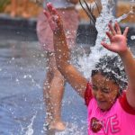 A young girl cools off in the fountain at Waterfront Park in downtown San Diego.