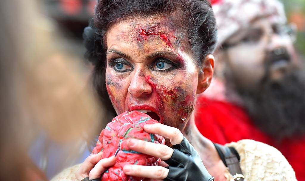 A zombie takes a break for a brain snack under the Gaslamp Quarter sign downtown.