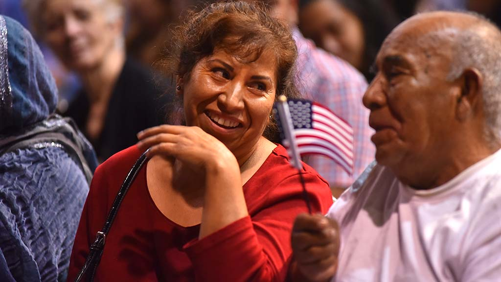 Immigrants share a moment at the oath ceremony for citizenship at Golden Hall.