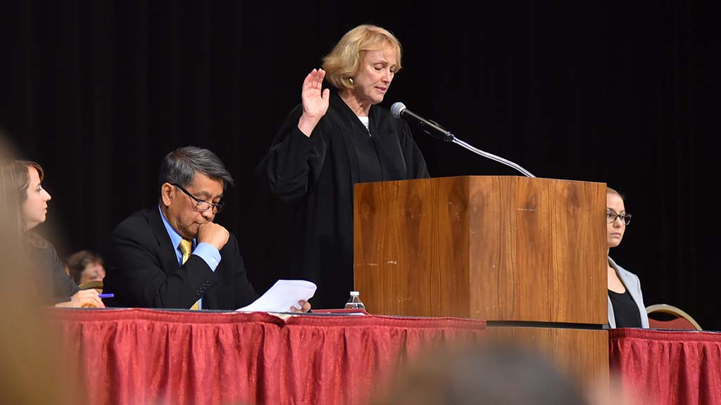 Magistrate Judge Barbara Major reads the oath as new citizens follow along.