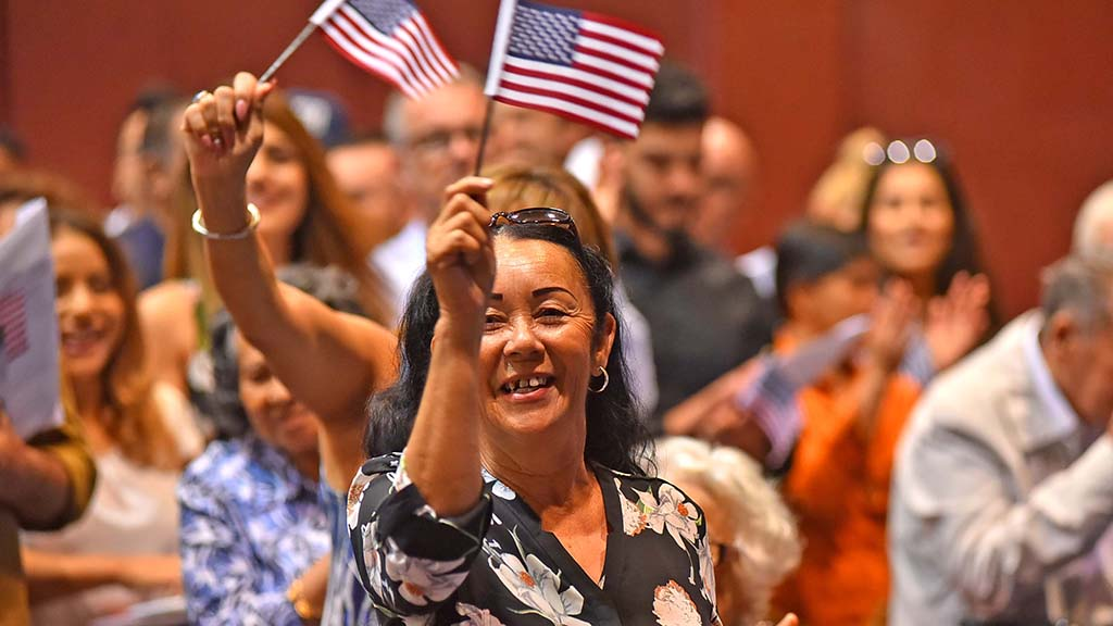 New citizens cheer after taking the oath at Golden Hall in downtown San Diego.